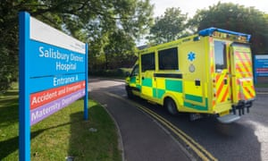 An ambulance drives past a sign for Salisbury district hospital
