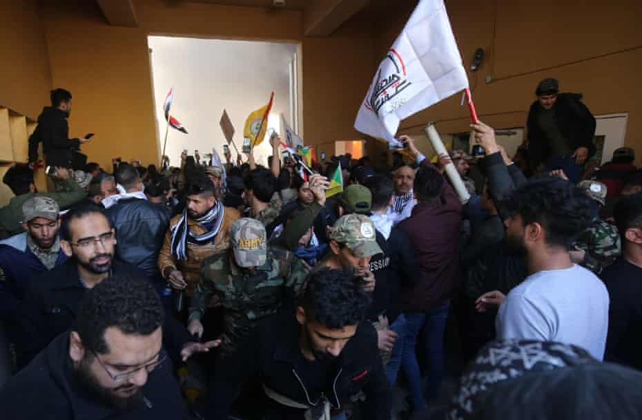 Iraqi protesters gather inside the security office at the entrance of the US embassy building in the capital Baghdad during a protest by Iraqis against the weekend's air strikes by US planes on several bases belonging to the Hezbollah brigades near Al-Qaim, an Iraqi district bordering Syria.