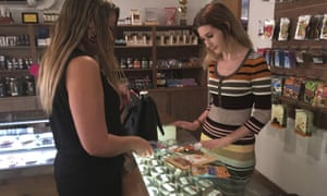 Golden State Greens 'budtender' Olivia Vugrin (right), serves a customer in San Diego, California. Dozens of shops in the state will be selling marijuana for recreational use from tomorrow.