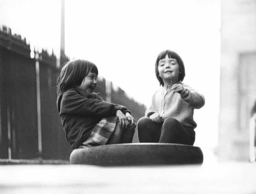 Two girls playing on tyre, Edinburgh, March 1966.