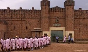 Wearing their distinctive pink uniforms, people suspected of involvement in Rwanda's 1994 genocide line up before re-entering Kigali's central prison from a day at work in the fields next to the prison