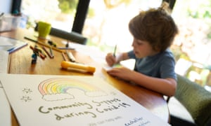"""Young child colouring at table, with poster reading: """"Community support during Covid-19"""" in foreground"""