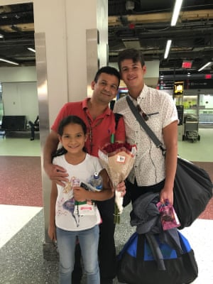 Guatemalan refugee Elmer is reunited with his two children, Eddy, 17, and Lilian, 9, at Logan international airport.