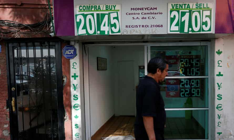 A man walks past a board displaying the exchange rate of the Mexican peso against the US dollar in Mexico City, on 9 January.