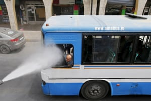 A bus driver is sprayed with water as part of an effort to combat the effects of a heatwave in Amman, Jordan