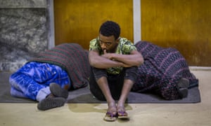 Zeynu Abebe, 19, sits between two sleeping people at Addis Ababa airport after being deported from Saudi Arabia