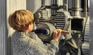 A young boy looks through a film camera at the Karel Zeman Museum in Prague.