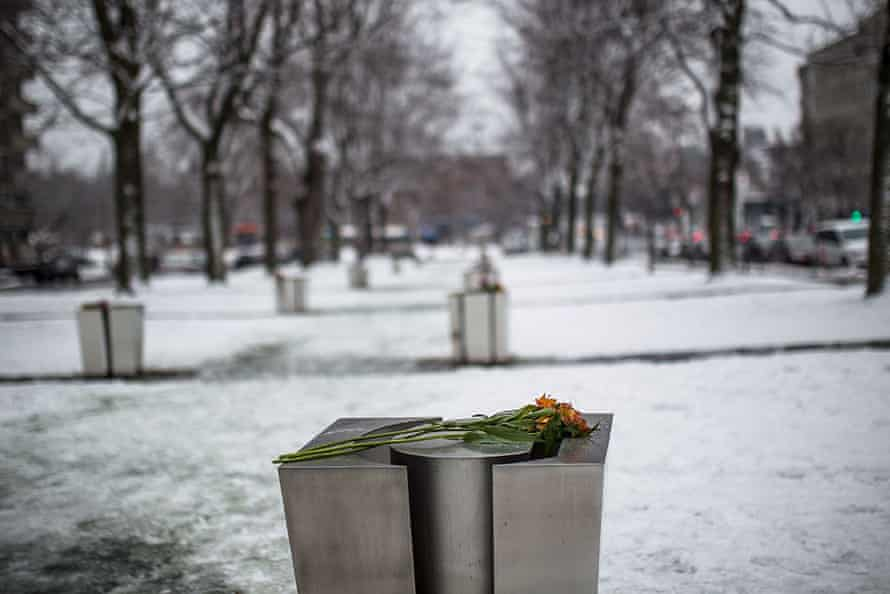 A flower is placed on a commemorative plaque to mark the 25th anniversary of the Ecole Polytechnique massacre in Montreal,
