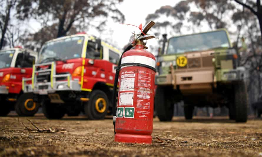 A fire extinguisher sits in front of a fire truck and an army vehicle at the CFA in Mallacoota, Australia January 10, 2020.
