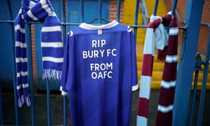 Football scarves and a shirt hang from the locked gates of Bury FC.