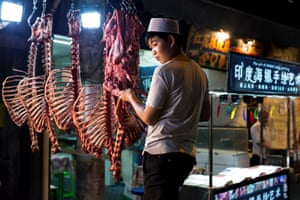 At night, a street food vendor prepares meat for his meals. Xi'an, north-west China. The Muslim quarter is busy, day and night, with street food vendors, serving dishes such as skewers of freshly butchered lamb cooked over charcoal grills.