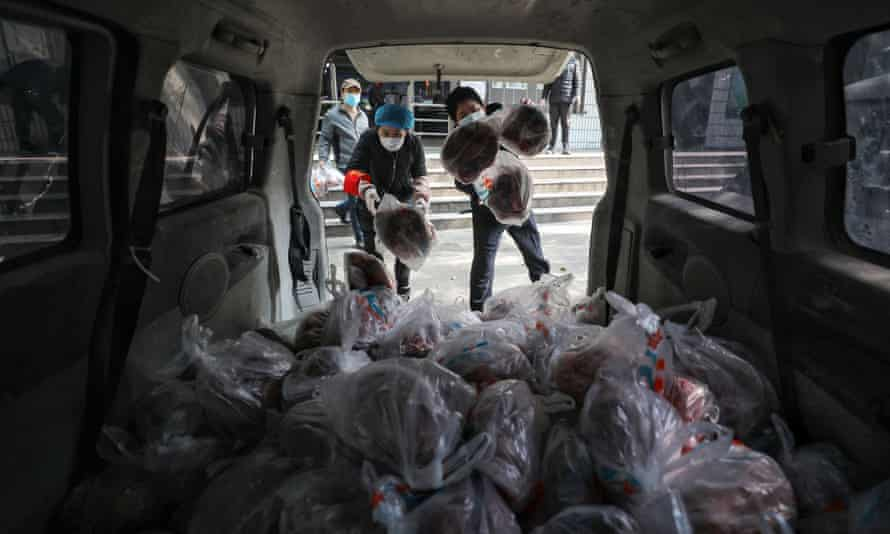 Supermarket workers prepare to deliver bags of vegetables to residents by van in Wuhan in China's central Hubei province on 5 March.