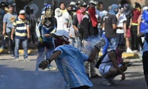 Anti-government protesters returns a tear gas canister during clashes with security forces on Wednesday.