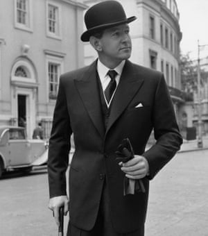 Man holding gloves and an umbrella, wearing a bowler hat and a tight-waisted suit