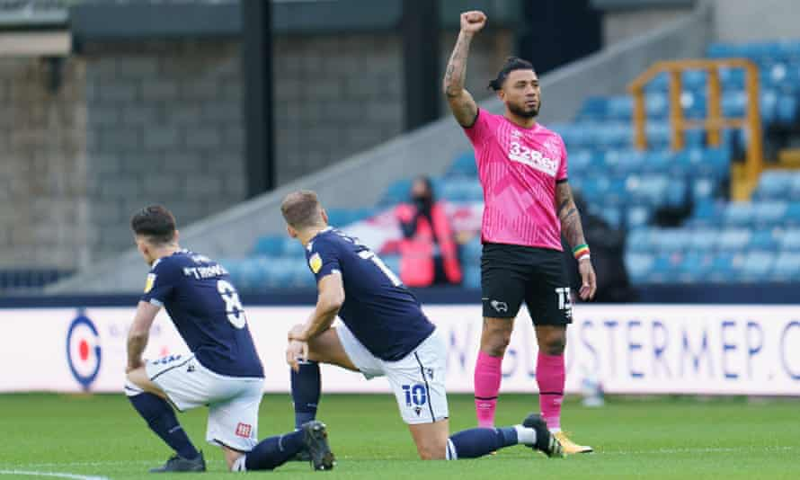 Millwall players take a knee while Derby's Colin Kazim-Richards stands in protest before the kick-off at the New Den.