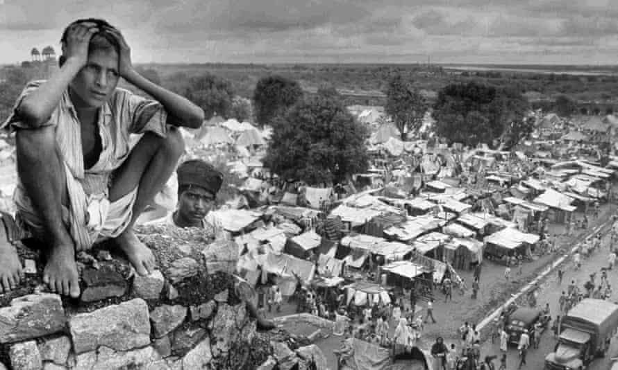 A boy sits on the walls of a refugee camp in Delhi during the Partition of India, 1947.