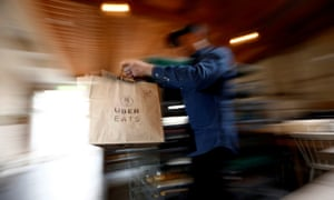 FILE PHOTO: A bag of donuts destined for delivery via Uber Eats is rushed to a driver from a kitchen in Sydney August 12, 2016. REUTERS/Jason Reed/File Photo
