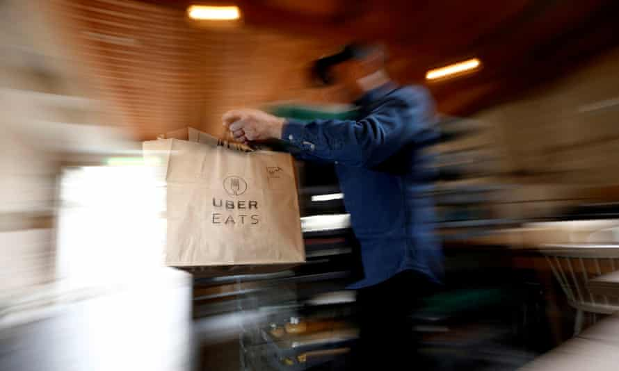 A bag of donuts destined for delivery via Uber Eats is rushed to a driver from a kitchen in Sydney.