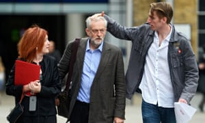 A member of Jeremy Corbyn's media team arranges his hair before speaking to reporters during the leadership election campaign.