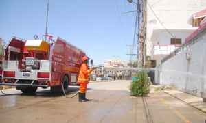 Pakistani workers spray disinfectants on a road in Hyderabad.