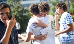 Linus Sheaff hugs Kai Ogdon (white t-shirt) after opening their GCSE exam results on GCSE results day at the City of London Academy, Hackney in London,