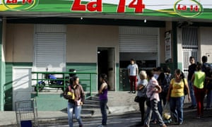 A supermarket with its security shutters partially closed as a precaution against looting in San Cristobal.