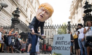A protester dressed as Boris Johnson digs a grave for British democracy