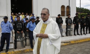 Father Edwin Román attempts to convince the police to allow relatives of imprisoned and dead anti-government demonstrators to enter the San Miguel Arcangel church in Masaya last week.