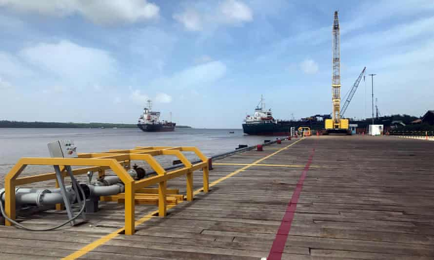 Ships carrying supplies for an ExxonMobil offshore oil platform leave the Demerara river south of Georgetown, Guyana.