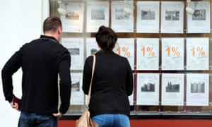 A couple looking at houses for sale in a estate agents window.