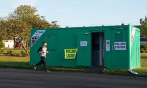 A runner passes a temporary building used as a polling station in Whitley Bay, North Tyneside