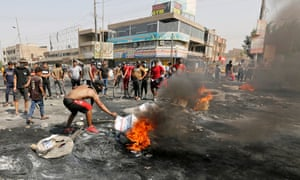 A demonstrator burns tyres during a curfew in Baghdad on Thursday.