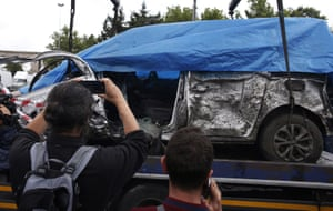 The remains of a car used in the blast is removed from the explosion site.
