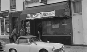 Four men entering the Mangrove, a Caribbean restaurant on All Saints Road, Notting Hill, London, 10 August 1970. The restaurant is seen here with a banner reading: 'Hands Off Mangrove' above it