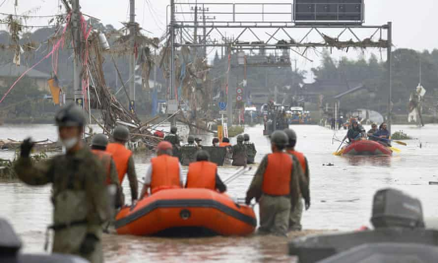 Local residents are rescued by soldiers using a boat at a flooding area caused by a heavy rain in Kuma village, Kumamoto prefecture.