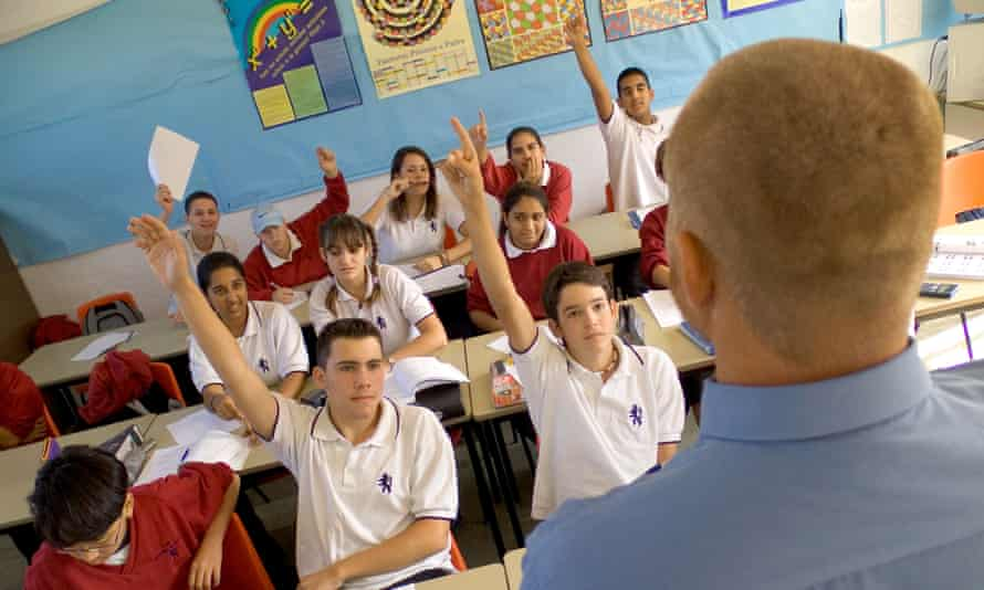 View over teacher's shoulder to enthusiastic teenage students with hands up in school classroom
