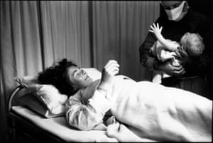 Newly Born Baby, 1956. A nurse handing a newborn to her mother