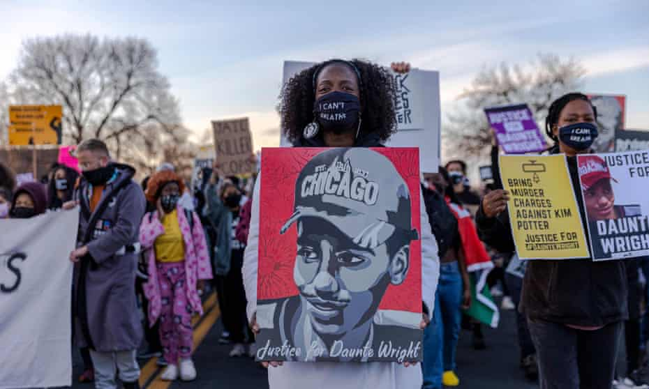 Demonstrators hold posters of Daunte Wright during a protest near the Brooklyn Center police department in Brooklyn Center, Minnesota 16 April 2021.