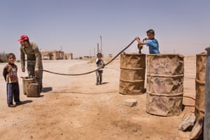 Members of a Bedouin family sell petrol from drums they have recovered
