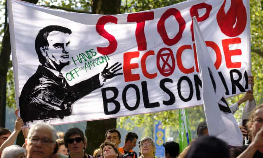 Activists hold up a banner of Jair Bolsonaro as they gather in front of the Brazilian embassy during a demonstration in Brussels, Belgium
