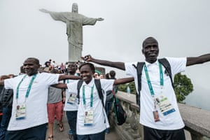 South Sudan's athlete Yiech Pur Biel (R), Rose Nathike Lokonyen (C) based in Kenya, and Kenyan coach Joseph Domongole for the Refugee Olympic Team (ROT) pose in front of the statue of Christ the Redeemer as the statue appears in fog ahead of Rio 2016 Olympic Games in Rio de Janeiro, Brazil, on July 30, 2016. The International Olympic Committee (IOC) selects 10 refugee athletes to set a refugee's team for the first time, to bring about hope to people displaced by conflicts or war in the world.