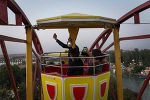 Young men take selfies while riding a ferris wheel.