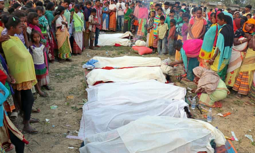 People gather around the bodies of tea plantation workers who died after drinking bootleg liquor in Golaghat, in the northeastern state of Assam, India, on Friday.