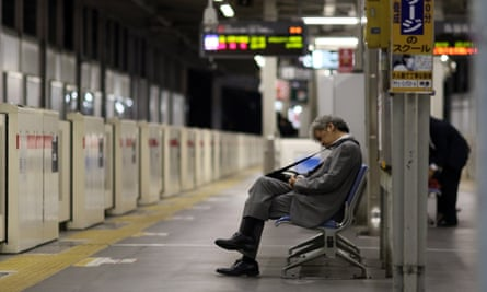 A businessman sleeping on a bench at a Tokyo train station.