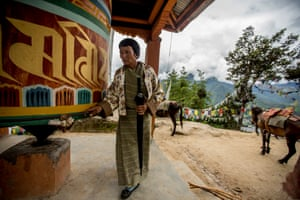 An elderly woman making the pilgrimage to Taktsang Monastery pauses for a moment of reflection at a prayer wheel