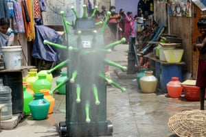 Residents watch as a coronavirus-themed robot sprays disinfectant in Chennai, India