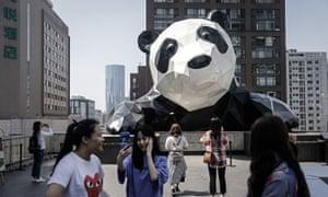 Tourists pose at a panda sculpture in Chengdu, Sichuan province, China.