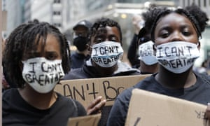 People with signs and masks reading 'I Can't Breathe'  are seen during a protest over the death of George Floyd in Chicago, Saturday 30 May, 2020.