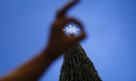 A tourist takes a souvenir photograph in front of a Christmas tree at a mall in Kuala Lumpur, Malaysia