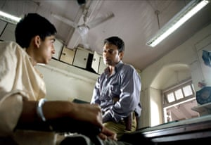 Khan as the police inspector, with Dev Patel in Slumdog Millionaire (2008)